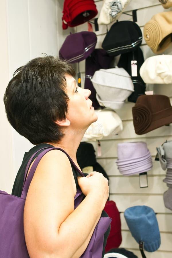 Γυναίκα στα καπέλα καταστημάτων στοκ φωτογραφίες με δικαίωμα ελεύθερης χρήσης