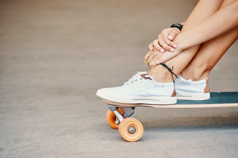 Γυναίκα στα πάνινα παπούτσια που οδηγούν skateboard υπαίθριο στην επιφάνεια ασφάλτου στοκ εικόνες