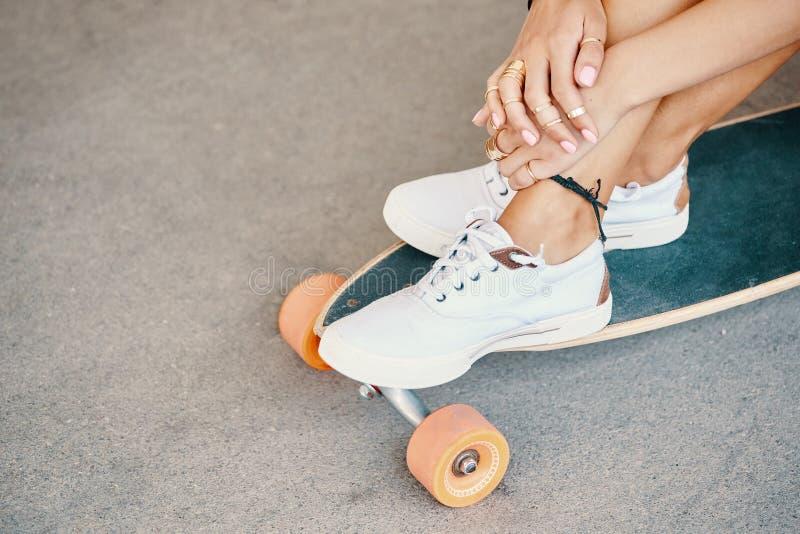 Γυναίκα στα πάνινα παπούτσια που οδηγούν skateboard υπαίθριο στην επιφάνεια ασφάλτου στοκ εικόνες με δικαίωμα ελεύθερης χρήσης