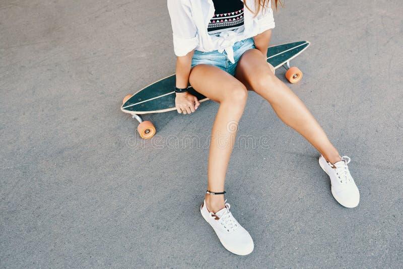 Γυναίκα στα πάνινα παπούτσια που οδηγούν skateboard υπαίθριο στην επιφάνεια ασφάλτου στοκ φωτογραφίες με δικαίωμα ελεύθερης χρήσης