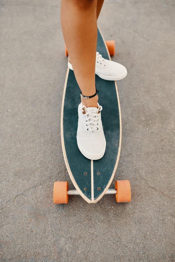 Γυναίκα στα πάνινα παπούτσια που οδηγούν skateboard υπαίθριο στην επιφάνεια ασφάλτου στοκ φωτογραφία με δικαίωμα ελεύθερης χρήσης
