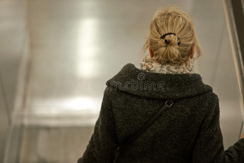 Γυναίκα στα σκαλοπάτια κυλιόμενων σκαλών στοκ εικόνες