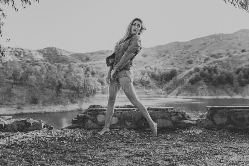 Γυναίκα στα σορτς και τοποθέτηση σακακιών στη φύση Τρύγος γραπτός στοκ εικόνα με δικαίωμα ελεύθερης χρήσης