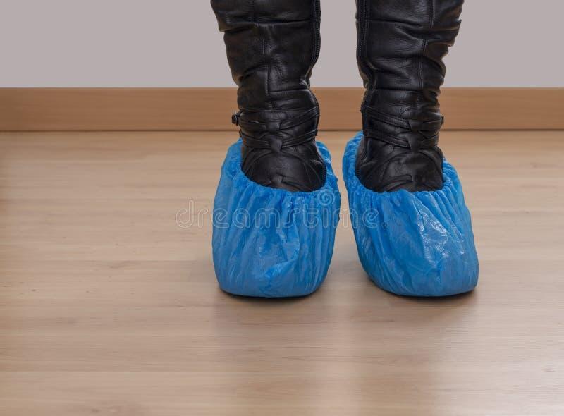 Γυναίκα στα τακούνια με τα πόδια στους μπλε πλαστικούς προστάτες παπουτσιών, καλύψεις Υγιεινή στις ιατρικές καταστάσεις κ.λπ. Μιά στοκ φωτογραφία με δικαίωμα ελεύθερης χρήσης