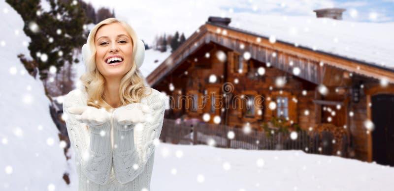 Γυναίκα στα χειμερινά καλύμματα αυτιών που παρουσιάζουν κενούς φοίνικες στοκ εικόνες