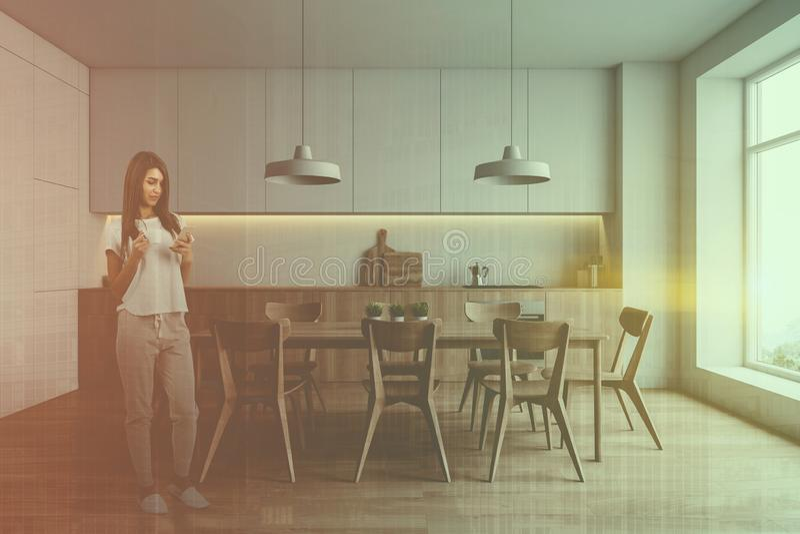 Γυναίκα στην άσπρη κουζίνα με τον πίνακα στοκ εικόνα με δικαίωμα ελεύθερης χρήσης