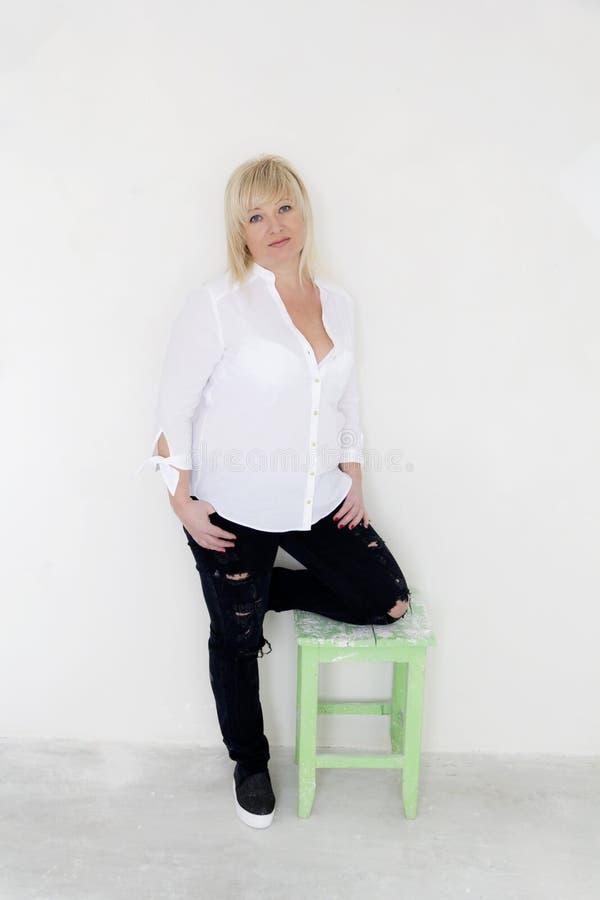 Γυναίκα στην άσπρη στάση στο γόνατό της μέσα στο κενό δωμάτιο στοκ φωτογραφία με δικαίωμα ελεύθερης χρήσης
