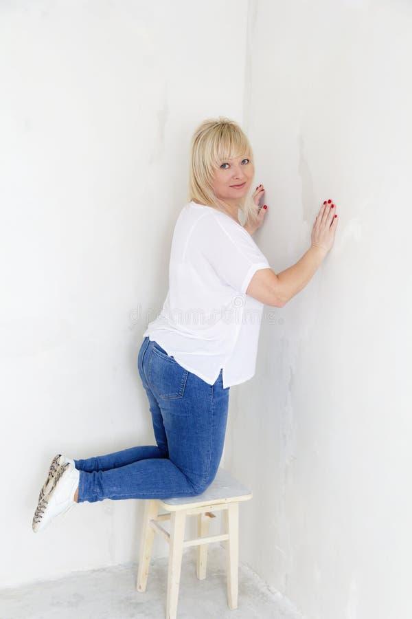 Γυναίκα στην άσπρη στάση στο γόνατό της μέσα στο κενό δωμάτιο στοκ εικόνες