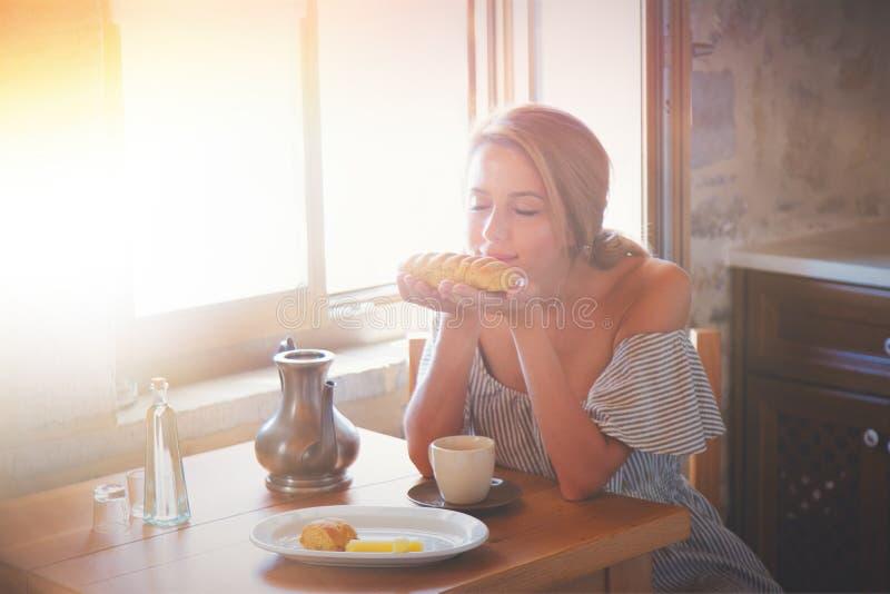 Γυναίκα στην αληθινή συνεδρίαση κουζινών σε έναν πίνακα με το ψωμί στοκ φωτογραφία με δικαίωμα ελεύθερης χρήσης