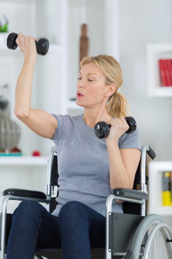 Γυναίκα στην αναπηρική καρέκλα που κάνει τη φυσιοθεραπεία στο σπίτι στοκ εικόνες