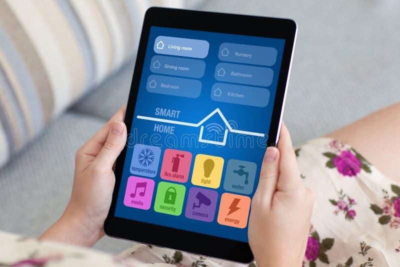 Γυναίκα στην ανθισμένη ταμπλέτα εκμετάλλευσης φορεμάτων με app το έξυπνο σπίτι στοκ φωτογραφίες