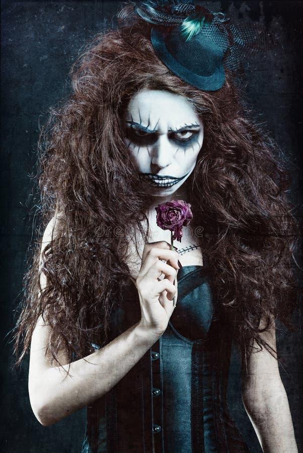 Γυναίκα στην εικόνα του γοτθικού φρικτού κλόουν με το μαραμένο λουλούδι Επίδραση σύστασης Grunge στοκ εικόνες με δικαίωμα ελεύθερης χρήσης