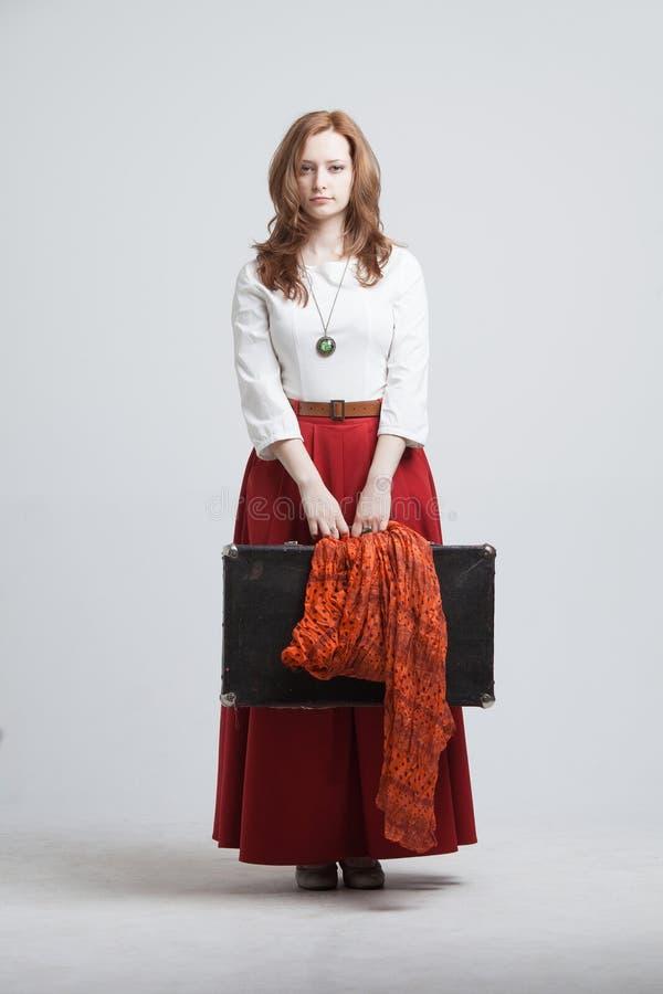 Γυναίκα στην εκλεκτής ποιότητας κόκκινη φούστα με μια βαλίτσα στοκ εικόνα με δικαίωμα ελεύθερης χρήσης