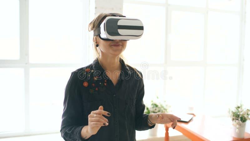Γυναίκα στην κάσκα VR που φαίνεται επάνω και που προσπαθεί να αγγίξει τα αντικείμενα στην εικονική πραγματικότητα στο σπίτι στο ε απόθεμα βίντεο