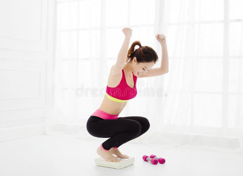 Γυναίκα στην κλίμακα βάρους που γιορτάζει weightloss στοκ φωτογραφία με δικαίωμα ελεύθερης χρήσης