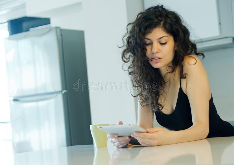 Γυναίκα στην κουζίνα με το PC ταμπλετών στοκ φωτογραφίες