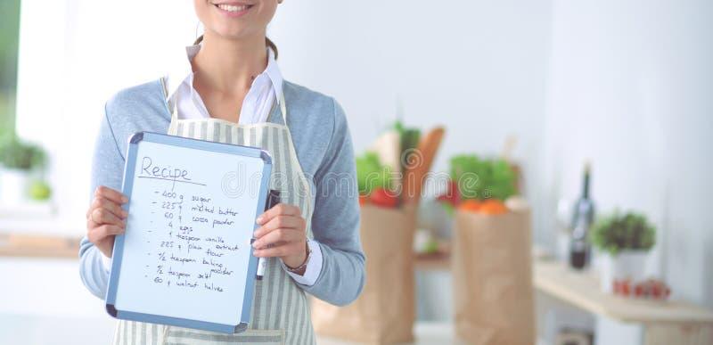 Γυναίκα στην κουζίνα στο σπίτι, που στέκεται κοντά στο γραφείο με το φάκελλο στοκ φωτογραφία