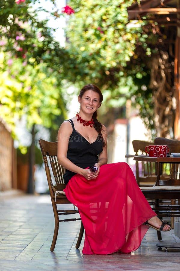 Γυναίκα στην κόκκινη συνεδρίαση φορεμάτων σε έναν καφέ πεζοδρομίων στοκ εικόνες