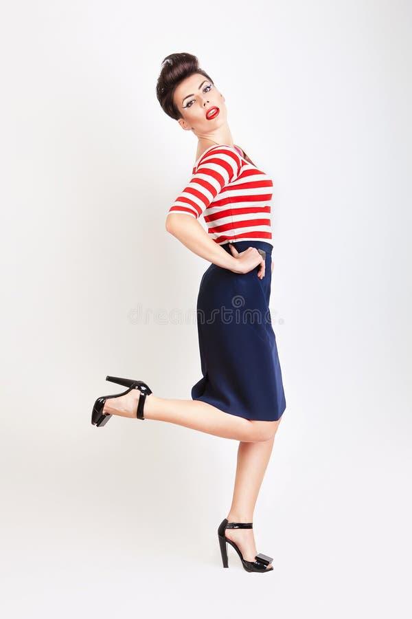 Γυναίκα στην μπλούζα και τη φούστα σε ένα πόδι στοκ φωτογραφίες