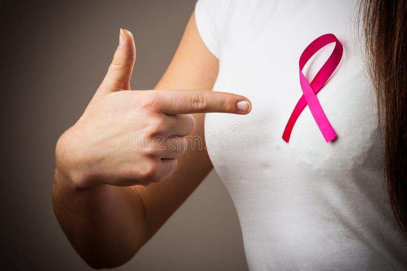 Γυναίκα στην μπλούζα με τη ρόδινη υπόδειξη κορδελλών καρκίνου στοκ φωτογραφίες με δικαίωμα ελεύθερης χρήσης