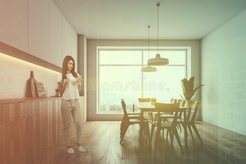 Γυναίκα στην πανοραμική κουζίνα με τον πίνακα στοκ φωτογραφία