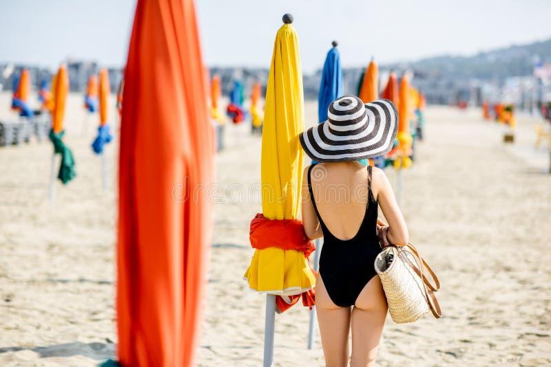 Γυναίκα στην παραλία με τις ζωηρόχρωμες ομπρέλες στη Γαλλία στοκ εικόνες