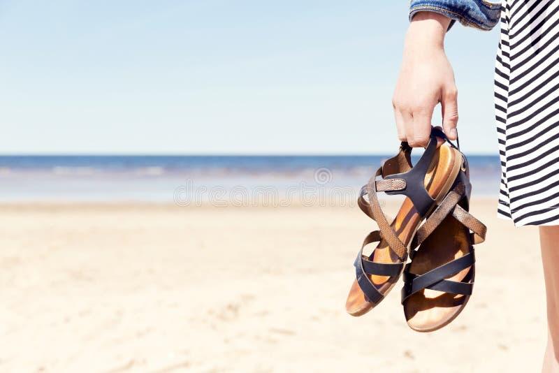Γυναίκα στην παραλία που κρατά τα σανδάλια της στην ηλιόλουστη θερινή ημέρα στοκ φωτογραφίες