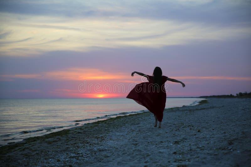 Γυναίκα στην παραλία στο ηλιοβασίλεμα στοκ φωτογραφίες