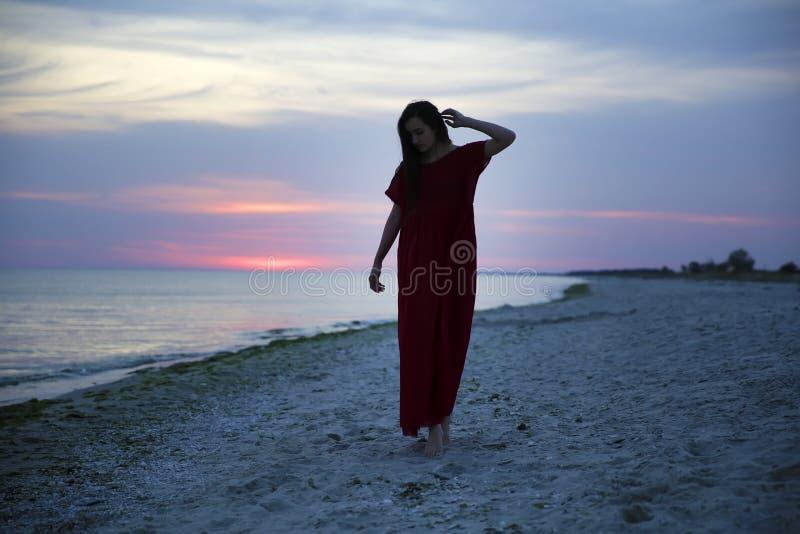 Γυναίκα στην παραλία στο ηλιοβασίλεμα στοκ εικόνες με δικαίωμα ελεύθερης χρήσης