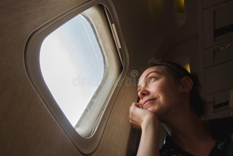 Γυναίκα στην παραφωτίδα στο αεροπλάνο στοκ εικόνα
