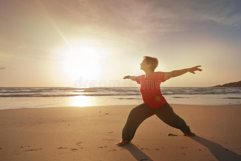 Γυναίκα στην παραλία που κάνει την ικανότητα στοκ εικόνες