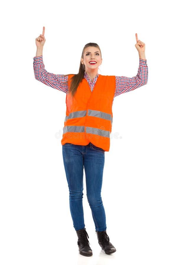 Γυναίκα στην πορτοκαλιά αντανακλαστική φανέλλα που δείχνει επάνω στοκ εικόνες με δικαίωμα ελεύθερης χρήσης