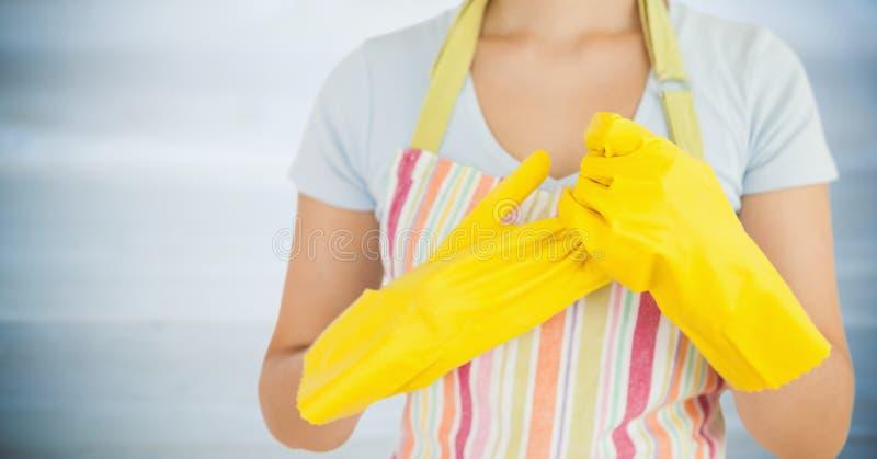 Γυναίκα στην ποδιά με τα κίτρινα γάντια επάνω ενάντια στη μουτζουρωμένη γκρίζα ξύλινη επιτροπή στοκ εικόνα με δικαίωμα ελεύθερης χρήσης