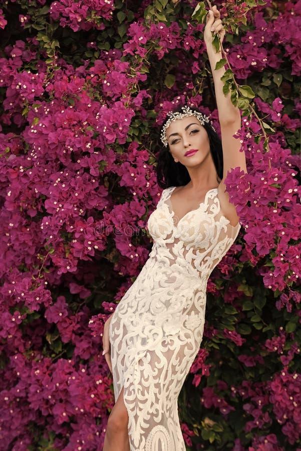 Γυναίκα στην τιάρα και το γαμήλιο φόρεμα Τοποθέτηση κοριτσιών στο ιώδες floral υπόβαθρο στοκ φωτογραφία με δικαίωμα ελεύθερης χρήσης