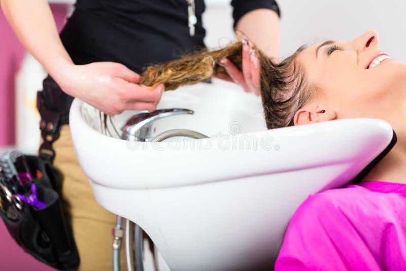 Γυναίκα στην τρίχα πλύσης κομμωτών στοκ φωτογραφίες με δικαίωμα ελεύθερης χρήσης