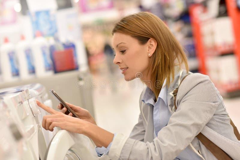 Γυναίκα στην υπεραγορά που επιλέγει το πλυντήριο στοκ φωτογραφία