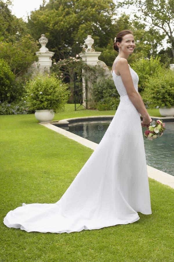 Γυναίκα στη γαμήλια εσθήτα σε Poolside στοκ εικόνα με δικαίωμα ελεύθερης χρήσης
