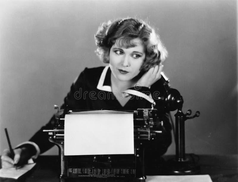 Γυναίκα στη γραφομηχανή στο τηλέφωνο (όλα τα πρόσωπα που απεικονίζονται δεν ζουν περισσότερο και κανένα κτήμα δεν υπάρχει Εξουσιο στοκ φωτογραφία με δικαίωμα ελεύθερης χρήσης