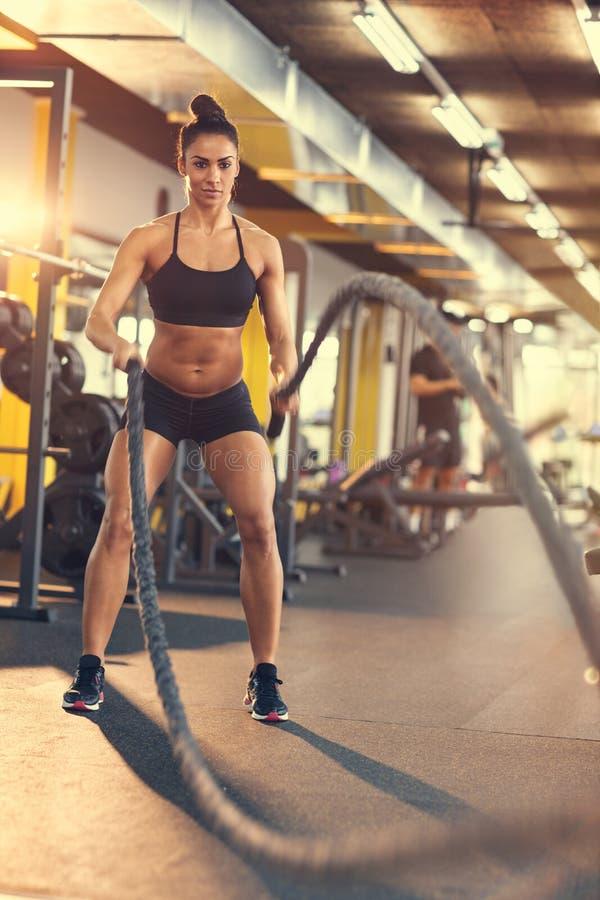Γυναίκα στη γυμναστική που χρησιμοποιεί το σχοινί για την άσκηση στοκ εικόνα
