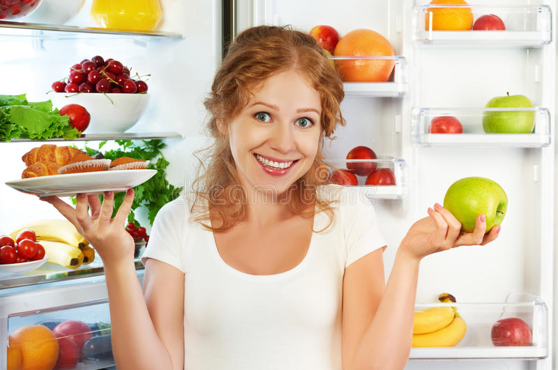 Γυναίκα στη διατροφή που επιλέγει μεταξύ των υγιών και ανθυγειινών τροφίμων πλησίον στοκ εικόνες