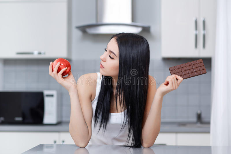 Γυναίκα στη διατροφή που κάνει την επιλογή των παλιοπραγμάτων ή των υγιών τροφίμων στοκ εικόνες