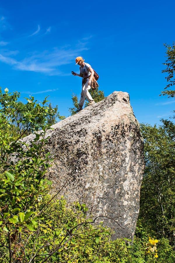 Γυναίκα στη μεγάλη πέτρα κατά τη διάρκεια της πεζοπορίας στοκ εικόνα