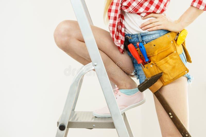 Γυναίκα στη σκάλα με το toolbelt στοκ εικόνες με δικαίωμα ελεύθερης χρήσης