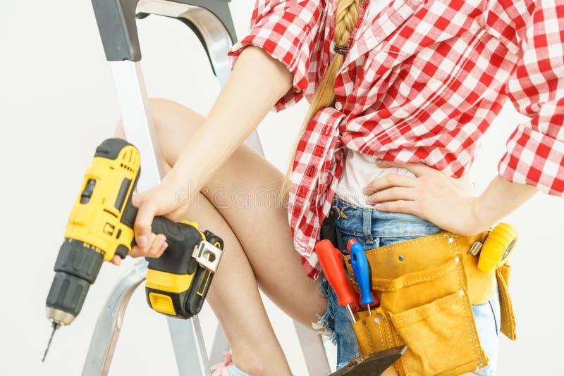 Γυναίκα στη σκάλα με το toolbelt στοκ φωτογραφίες