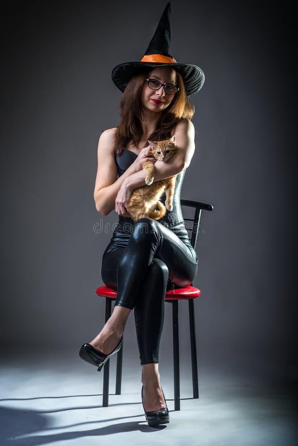 Γυναίκα στη συνεδρίαση κοστουμιών μαγισσών σε μια καρέκλα και την εκμετάλλευση ένα γατάκι, υπόβαθρο αποκριές στοκ φωτογραφίες