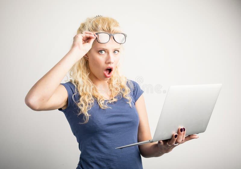 Γυναίκα στη δυσπιστία που ανυψώνει επάνω τα γυαλιά της και που κρατά το lap-top στοκ εικόνες με δικαίωμα ελεύθερης χρήσης