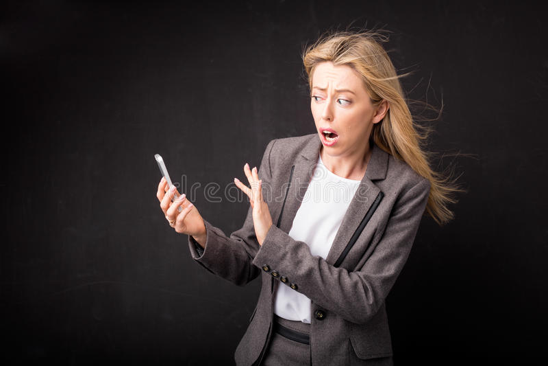 Γυναίκα στη φρίκη που κλίνει μακρυά από το κινητό τηλέφωνο της στοκ εικόνες