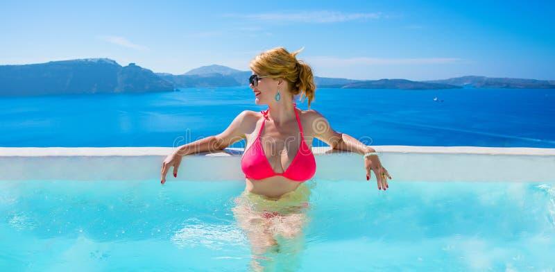 Γυναίκα στη χαλάρωση μπικινιών στην υπαίθρια λίμνη πολυτέλειας στοκ φωτογραφία με δικαίωμα ελεύθερης χρήσης