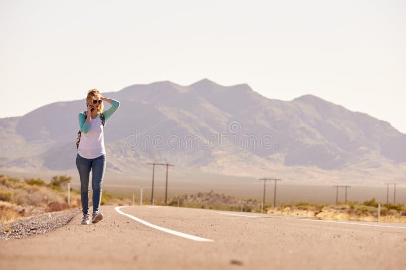 Γυναίκα στις διακοπές που κάνει ωτοστόπ κατά μήκος του δρόμου που χρησιμοποιεί το κινητό τηλέφωνο στοκ φωτογραφία με δικαίωμα ελεύθερης χρήσης
