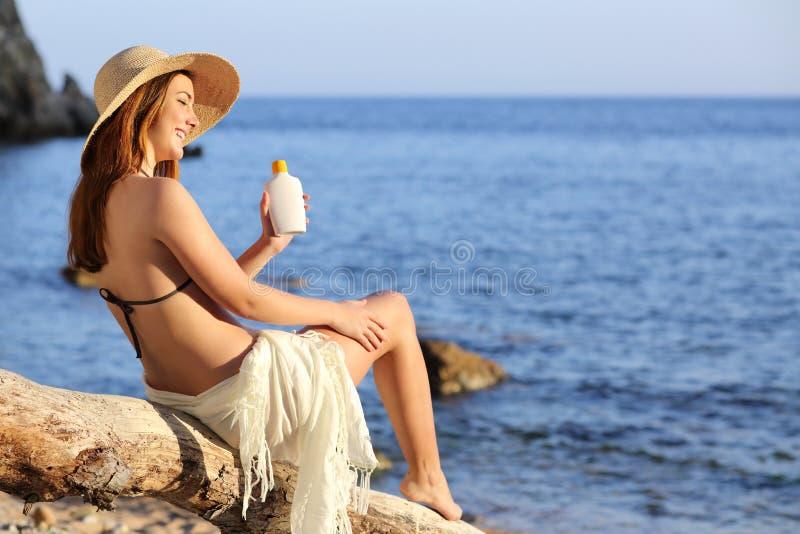 Γυναίκα στις διακοπές στην παραλία που εφαρμόζει sunscreen την προστασία στο πόδι στοκ φωτογραφία